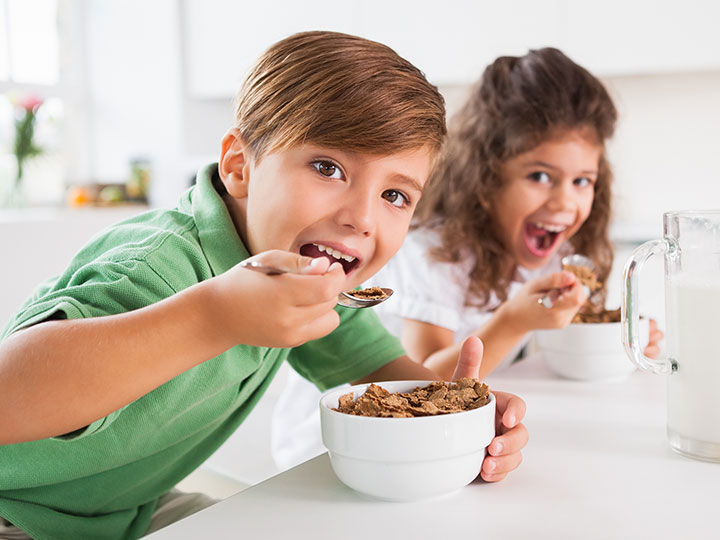 two children having cereal breakfast happy healthy growing up